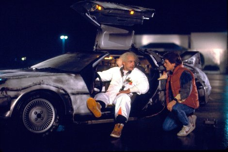 Doc Brown and Marty McFly chat outside the famous DeLorean.