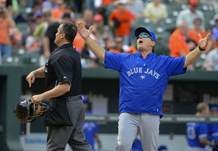 Toronto Blue Jays manager John Gibbons (R) reacts as he gets ejected from the game by umpire Mike DiMuro for arguing a called strike three on batter Brett Lawrie from Baltimore Orioles relief pitcher Troy Patton to end the top of the ninth  inning of their MLB American League baseball game in Baltimore, Maryland April 24, 2013.  REUTERS/Doug Kapustin (UNITED STATES - Tags: SPORT BASEBALL)