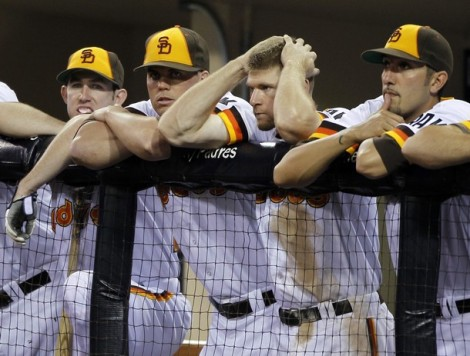 San Diego Padres third baseman Chase Headley holds his head as he hands at the dugout fence as he stands with teammates in the ninth inning during a loss to the Chicago Cubs in their MLB National League baseball game in San Diego